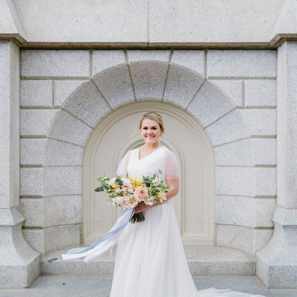 Lauren, our #BitsyBride, in her flutter sleeve A-line modest wedding gown.  Photography by Mikki Platt.
