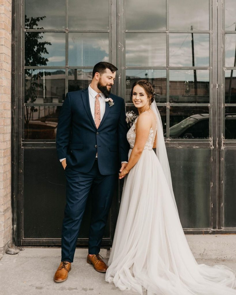 McKenzie, our real #BitsyBride is holding hands with her new husband and is turned towards him, looking over her shoulder. McKenzie paired and English net veil with her perfect wedding dress from Bitsy Bridal.