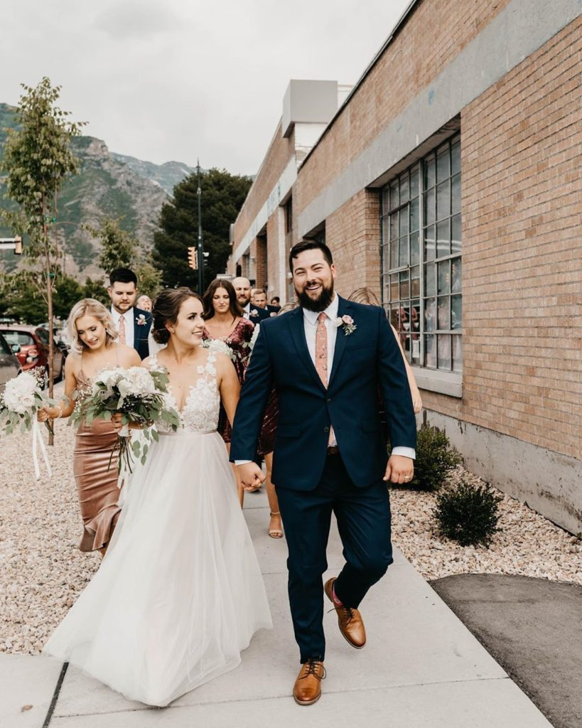 McKenzie in her perfect wedding dress, with her new husband. The happy couple is holding hands and is followed by their wedding party and guests.