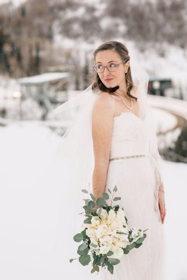 The bride is wearing a lace fit and flare wedding dress.